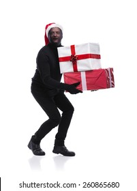 Thief in action carrying presents with balaclava on his face, dressed in black. Studio shot on white background.