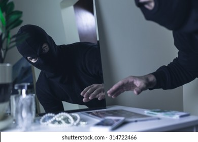 Thief in balaclava breaking into the house