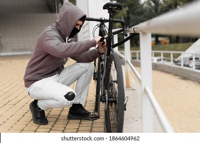 A thief in a balaclava and a hood breaks the lock on a bicycle in the street during the day. Closed face and hacking. Stealing bicycles.
