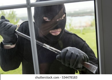 A thief in a black mask breaks apartment window.