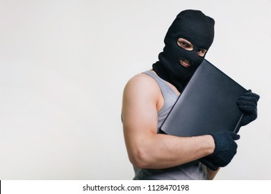A thief in a black mask stole a laptop. A man in a balaclava and with a computer in hands on a white background. The hacker is hacking the computer. Steals information. A young man breaks the law.