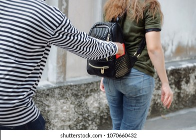 thief in black and white jacket stealing the wallet or mobile phone from behind young caucasian woman traveling bag on street in big city, thief, crime, robber and steal concept