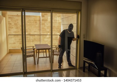 Thief breaks into the apartment through the unlocked sliding door on the balcony. He wearing black clothes and balaclava