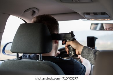 A thief, a criminal with a pistol threat, tries to steal a car, sits at the passenger's seat and holds a pointed gun in the driver's car