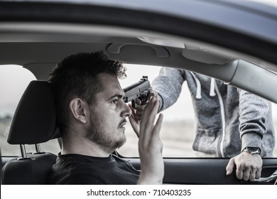 A thief, a criminal with a pistol threat, is trying to steal a car, holding a pointed gun in a car driver, hijacking, car theft