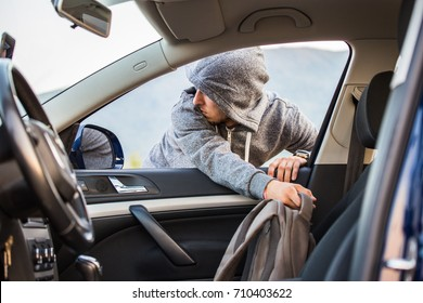 A thief, a criminal, thrust his hand out of the car window and takes a backpack, steals private property, whether the passers-by do not notice him in theft