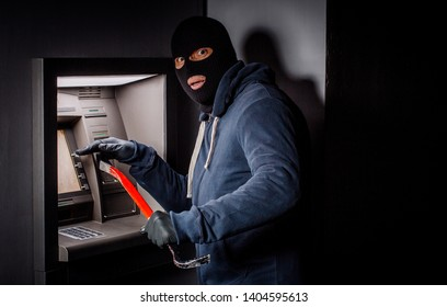 thief with crowbar opens the ATM.