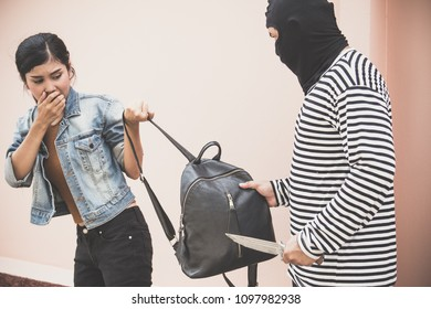 Thief Dangerous man or masked robber with knife attacking shoulder bag. Robber or thief holding knife burglarize to steal the money wallet in woman's bag,