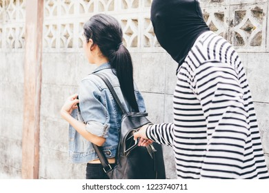 Thief Dangerous man or masked robber with knife attacking shoulder bag. Robber or thief holding knife burglarize to steal the money wallet in woman's bag, while standing near her car and don't careful