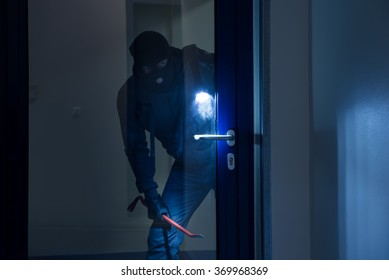 Thief with flashlight trying to break glass door with crowbar