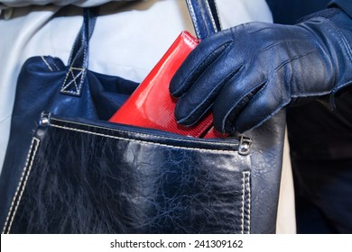 Thief in gloves stealing a purse  from the women's bags