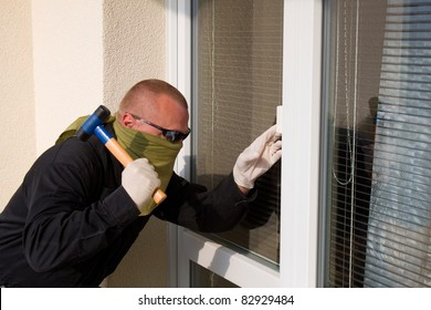 thief with a hammer smashing a glass door