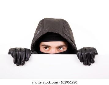 Thief hiding under a white wall