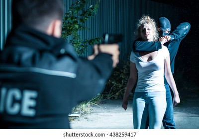 Thief holding a woman hostage while a policeman is pointing gun at him