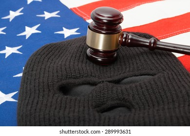 Thief mask and judge gavel over US flag