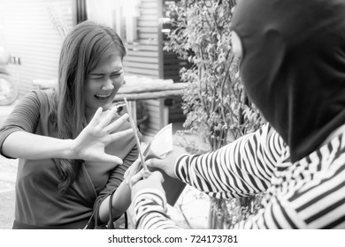 The thief or robber is using and pointing the knife threatened a beautiful woman and telling her for sending money. A beautiful girl is screaming and scaring with black and white photo