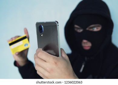 The thief scammer is holding a mobile phone and credit card. The concept of Bank card fraud through a virus in the smartphone. a thug in a black Balaclava and a black hood