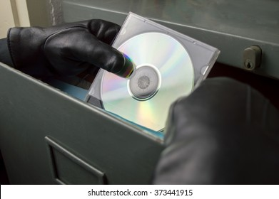 thief stealing in a digitized office files in  compact disk