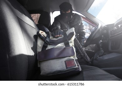 Thief stealing handbag from car