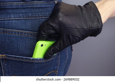 Thief is stealing mobile phone from back pocket of a woman.
