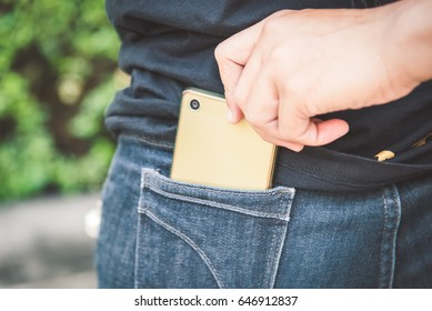 Thief stealing the mobile phone from the blue jeans pocket of a woman