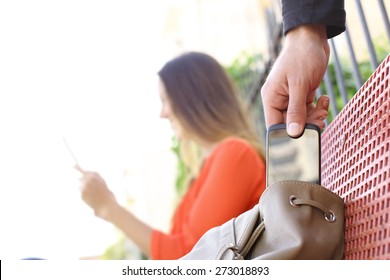 Thief stealing a mobile phone to a woman sitting on a bench in a park