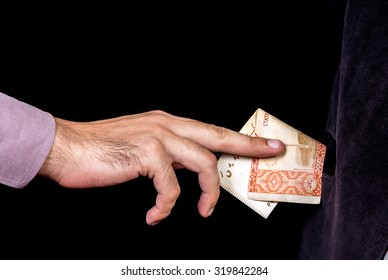 thief stealing money by reaching his hand picking up 5000 banknote from coat pocket  isolated with black background