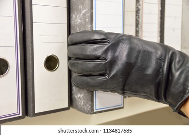 thief stealing ring binder and confidential files in an office