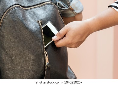 Thief stealing using his hand to pick up the mobile phone from the back pocket of the victim.
