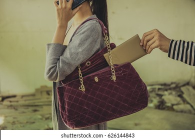 Thief stealing the wallet from the bag of a distracted woman.,Stealing.,hand stealing a purse from the bag on red