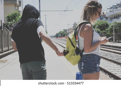 Thief is stealing the wallet to a girl at the station