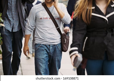 Thief stealing wallet from man's handbag while he's talking on the mobile phone. Pickpocketing on the street during daytime