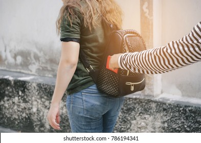 thief stealing the wallet or mobile phone from behind young caucasian woman bag on street, thief, crime, robber and steal concept