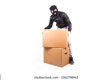 Thief steals brown boxes. Young man in front of a white background. A person with two boxes. Masked gangster with a black jacket.