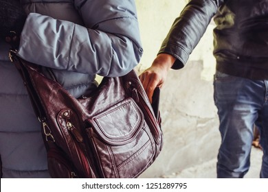 Thief steals phone or smartphone from bag of  woman close up, pickpocket in city concept