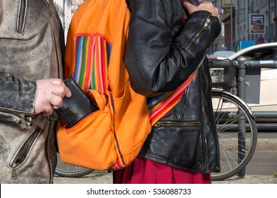 A thief takes a phone from a backpack