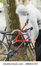 Thief Trying To Break The Bicycle Lock With Long Pliers
