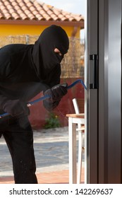 Thief trying to force a window to rob a house