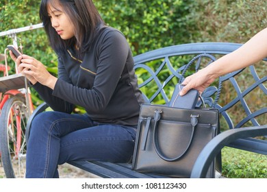 Thief trying to steal and walk away the wallet while woman using mobile phone and sitting on chair.