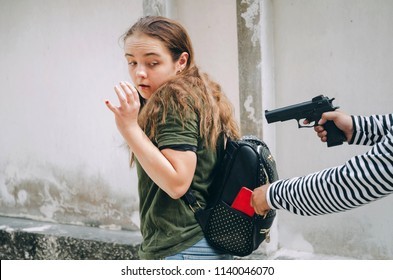 thief using the gun for stealing the wallet or mobile phone from behind young caucasian woman bag on street, thief, crime, robber and steal concept