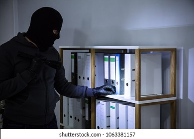 Thief Wearing Balaclava Stealing File From Shelf At Workplace