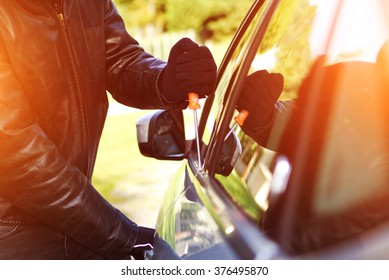 Thief wearing black clothes and leather coat stealing a car
