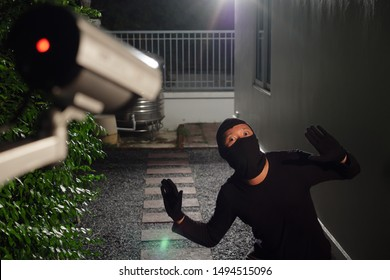 Thief wearing black suit with balaclava and glove being caught by CCTV, surveillance camera during sneak into a house at night