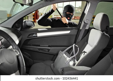 A thief wearing a robbery mask trying to steal a purse bag in a automobile