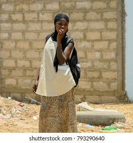 THIES, SENEGAL - APR 26, 2017: Unidentified Senegalese woman in black headscarf puts her fingers into her mouth in Thies, the third largest city in Senegal