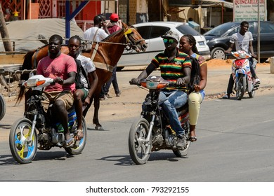 THIES, SENEGAL - APR 26, 2017: Unidentified Senegalese men ride on the motorcycles, a popular transportation way in Africa