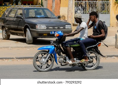 THIES, SENEGAL - APR 26, 2017: Unidentified Senegalese man rides on a motorcycle, a popular transportation way in Africa
