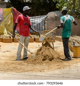 THIES, SENEGAL - APR 26, 2017: Unidentified Senegalese two men dig with shovel in Thies, the third largest city in Senegal