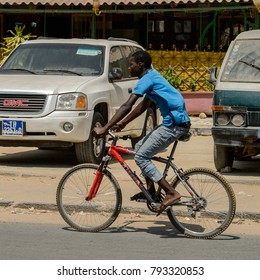 THIES, SENEGAL - APR 26, 2017: Unidentified Senegalese boy rides a bicycle, a popular transportation way in Africa