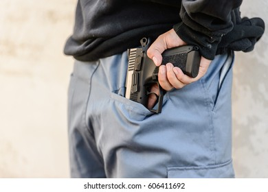 Thieves are taking their guns out of their pockets in preparation for the robbery.